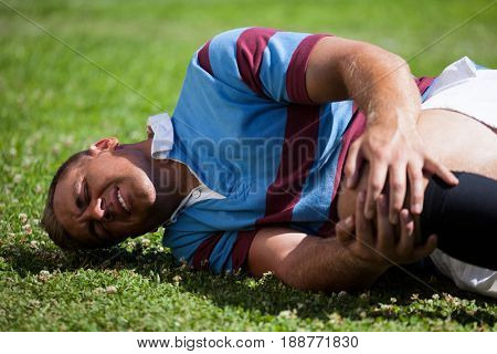 Injuerd young rugby player lying on playing field