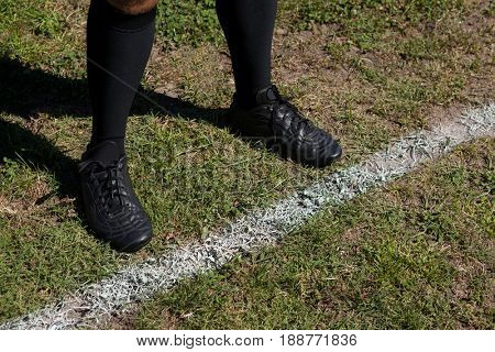 Low section of rugby player standing by yard line on field during sunny day