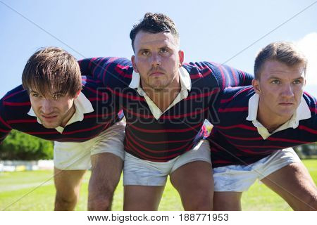 Close up of rugby players bending while standing at field against sky