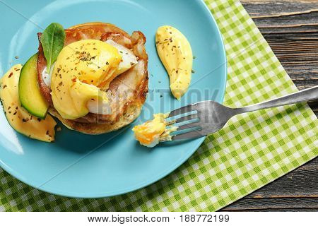 Egg Benedict with fork on plate, closeup