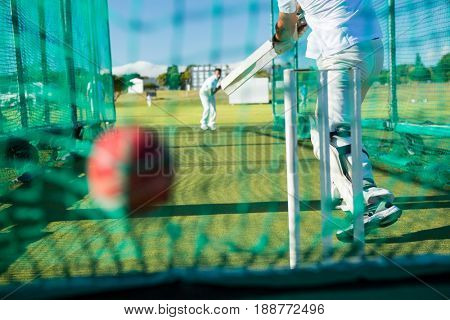 Low section of spoertsman playing cricket at field on sunny day