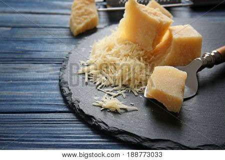 Slate plate with cheese and shovel on wooden table