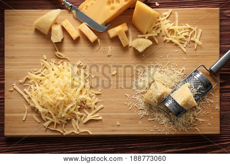 Cutting board with cheese, grater and knife on wooden background