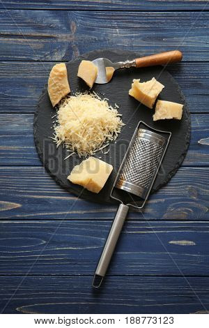 Slate plate with cheese and grater on wooden background
