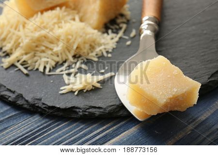 Shovel with piece of tasty cheese on table, closeup