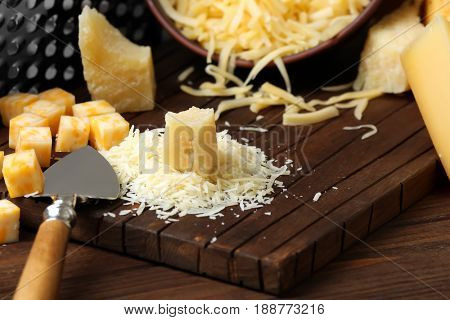 Cutting board with grated cheese on wooden table