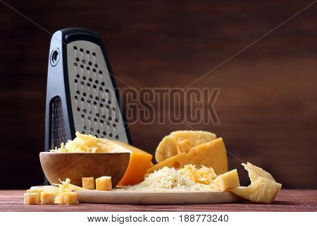 Cutting board, bowl with cheese and grater on wooden background