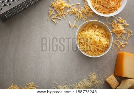 Bowls with delicious cheese and grater on light background