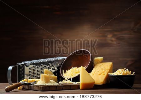 Composition of grater, cutting board and bowls with cheese on wooden background