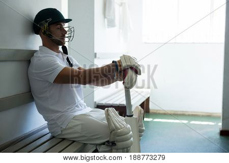 Close up of cricket player sitting on bench at locker room
