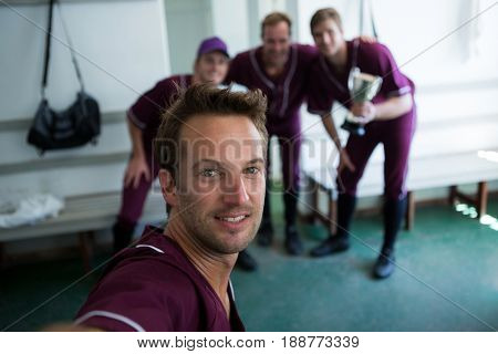 Portrait of smiling baseball team clicking selfie while standing at locker room after match