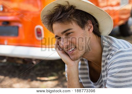 Thoughtful man sitting in the park with camper van in background