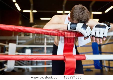 Defeated kick-boxer leaning on boxing-ring rope