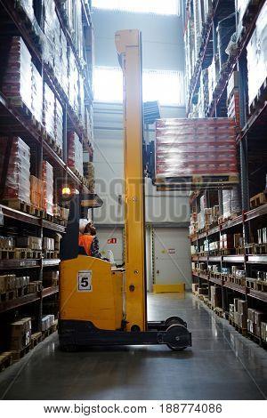 Loader lifting packed goods on shelf of storehouse