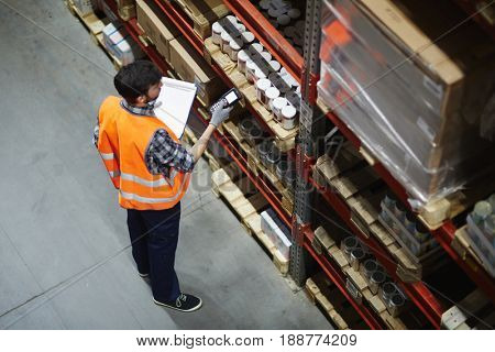 Logistics dispatcher scanning barcodes on packs with goods