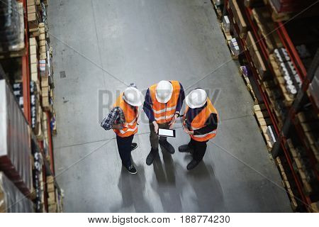 Team of warehouse workers with touchpad making revision of goods