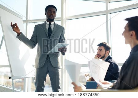 Portrait of successful African businessman pointing at whiteboard  during presentation meeting
