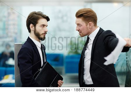 Angry boss shouting at one of employees