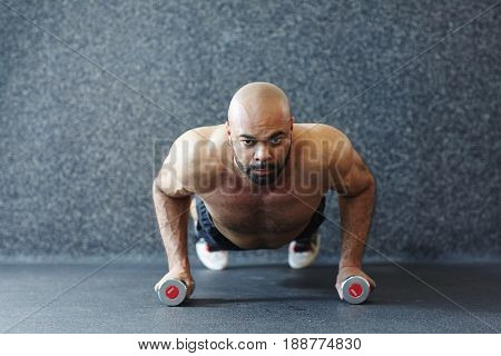 Young man with dumbbells doing planks