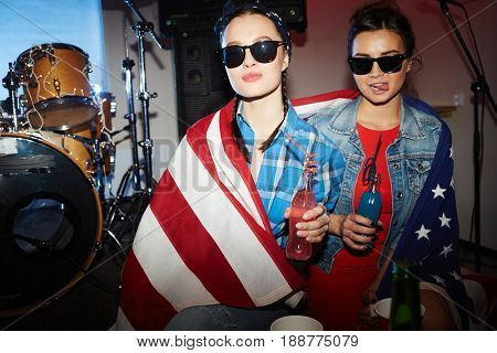 Two girs in sunglasses holding bottles with drinks