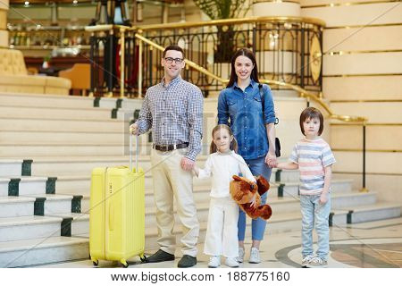 Happy family of four with baggage standing by staircase in hotel lobby