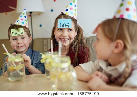Happy kids with notepapers on foreheads playing guess game