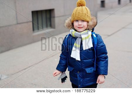 Adorable youngster in winterwear looking at camera