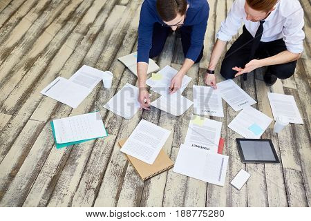 Assorted documents and contracts laid out on wooden office floor with  two business  people busy working
