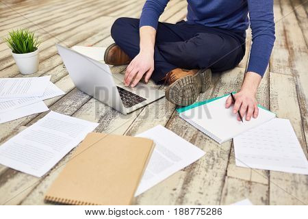 Unrecognizable modern freelancer  sitting cross legged on wooden floor, using laptop computer while working with documents