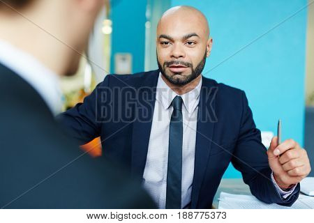 Portrait of charismatic bald businessman talking to partner in meeting, discussing work, looking very confident and successful