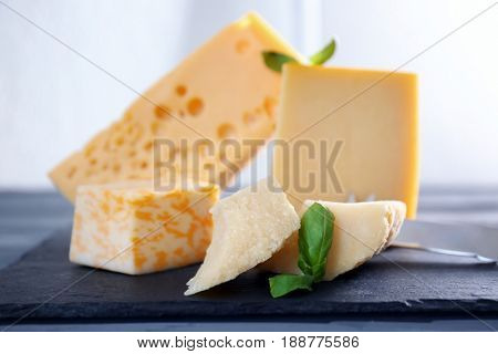 Slate plate with different pieces of  cheese on table