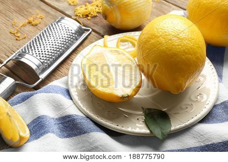 Plate with lemons and grater on wooden table, closeup