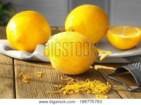 Composition with lemons and zest on wooden table, closeup
