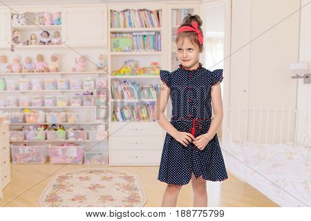Cute little girl in a short blue dress with polka dots. With a red bandage on his head.Close-up.In the children's room.