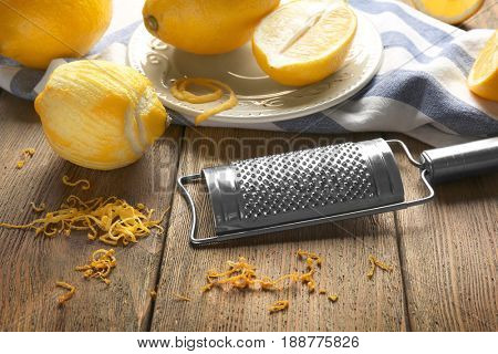 Grater and lemons on wooden table