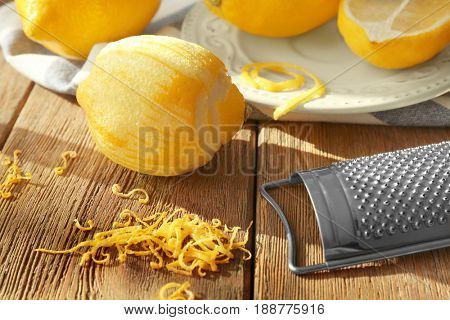 Grater, peeled lemon and zest on wooden table, closeup