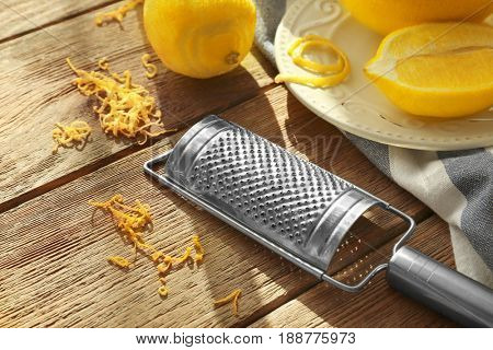 Grater, lemons and zest on wooden table, closeup