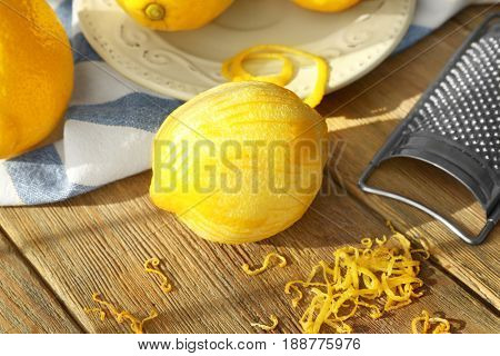Peeled lemon, zest and grater on wooden table