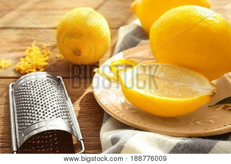 Lemons and grater on wooden table, closeup