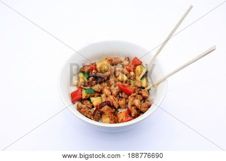 Kung Pao Chicken. White Ceramic Bowl with Steamed White Rice, Chinese Kung Pao Chicken, Vegetables and Chopsticks on a white background. Chinese fast food.