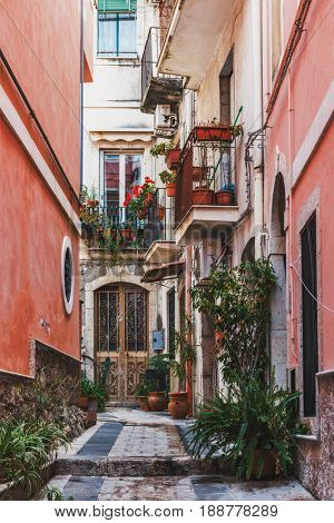 TAORMINA, SICILY, ITALY - APRIL 27, 2017: Picturesque cobbled walkway in Taormina, Sicily, Italy with potted plants, geraniums and balconies between colorful red walls