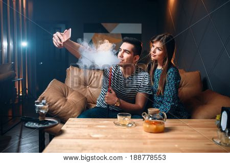 Love couple smokes hookah at the bar