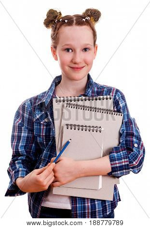 Cute girl in a blue checkered shirt holding a blue pencil and notepads for drawing, isolated on a white background.