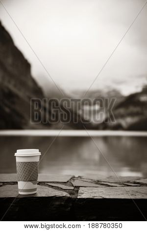 Lake Louise with coffee cup in Banff national park with mountains and forest in Canada.