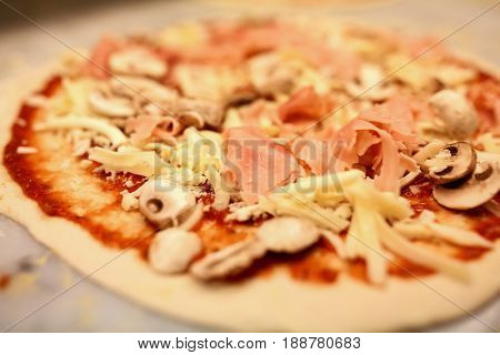 food, culinary, italian cuisine and cooking concept - close up of raw pizza with grated cheese, ham and champignons