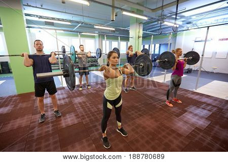 fitness, sport, training, exercising and lifestyle concept - group of people with barbells doing standing shoulder press in gym