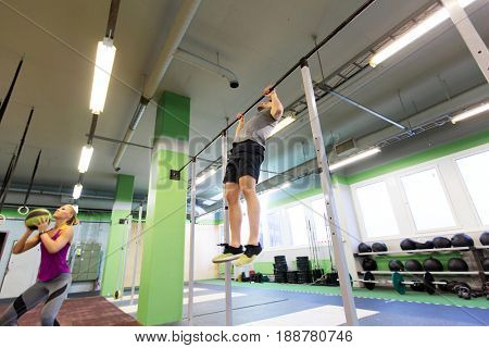 fitness, sport and training concept - woman and man with medicine ball and horizontal bar exercising in gym