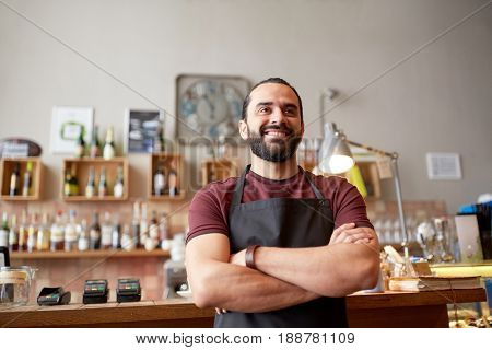 small business, people and service concept - happy man or waiter in apron at bar or coffee shop