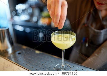 alcohol drinks, people and luxury concept - woman bartender with glass preparing cocktail at bar
