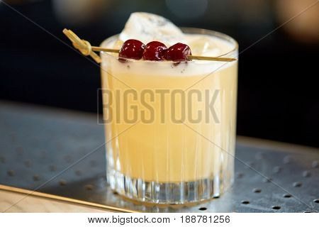 alcohol drinks and luxury concept - glass of cocktail with cherries at bar